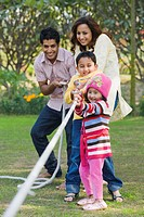 Couple with their children playing tug_of_war in a park