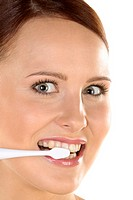 Beautiful woman cleaning her teeth by electrical toothbrush