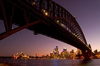 The Sydney skyline at sunset framed by the Harbour Bridge from North Sydney