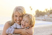Mid adult woman hugging her son and smiling