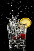Cherries splashing into sparkling water glass with lemon slice on black background