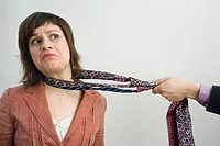 Close_up of a person´s hand pulling a businesswoman with her tie