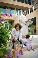 Young couple reading newspapers with their daughter, San Diego, California, USA