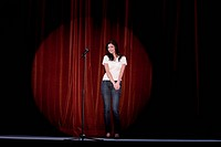 young woman standing on stage behind microphone