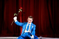 comedian sitting on stage holding red rose