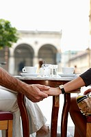 detail of couple sitting at cafe table holding hands