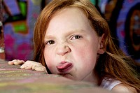 portrait of young girl behind wall sticking out tongue