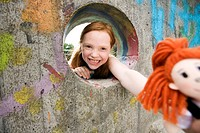 portrait of laughing girl looking through hole in wall on playground holding doll