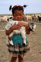 Portrait of mongolian little girl holding a lamb in her arms, Mongolia
