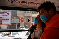 Mexico City, Mexico, April 29, 2009: Scared and wearing masks to protect against a Swine Flu outbreak, Mexicans nervously ride a bus. Over 200 people ...