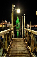 Wooden pier for docking of Venetian gondolas in the dark of night by lanterns iluninadas a lantern decorated with green and gold background