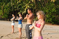 People practicing yoga on a beach