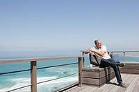 Senior man on balcony by the sea