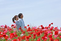 Young Couple Enjoying in Field of Red Flowers