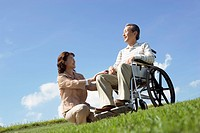 Senior woman crouching by her husband in wheelchair at the park