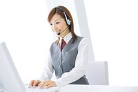 Smiling businesswoman wearing headset and typing on computer