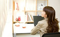Businesswoman sitting at desk in office with laptop
