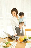 Woman using laptop with baby sitting in her lap
