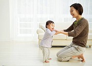 Woman teaching her baby to walk