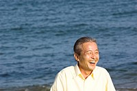 Senior man laughing at the beach