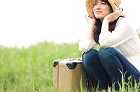 Woman sitting in field with suitcase