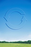Recycling symbol in blue sky over field and trees