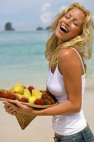 young blond woman on beach with tropical fruits in Thailand