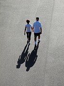 Middle-aged couple walking for exercise in the early morning sun