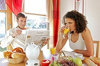 couple having breakfast together he reads newspaper she is annoyed