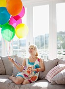 Woman holding balloons on sofa in living room (thumbnail)