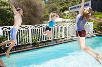Friends jumping into swimming pool