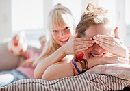 Woman covering friend's eyes (thumbnail)