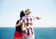 Couple hugging and pointing towards ocean
