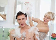 Woman playing with soap suds on man in bathroom