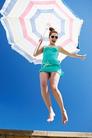 Woman holding beach umbrella and jumping off ledge