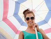 Woman in sunglasses holding beach umbrella