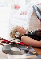 Woman laying on floor listening to headphones and holding record