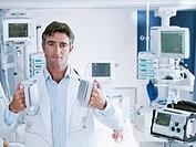Doctor holding defibrillator paddles in hospital room