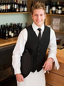 Waiter leaning on counter in restaurant