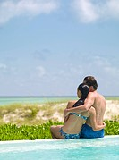 Couple sitting at edge of swimming pool, hugging and looking at ocean