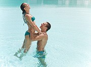 Man lifting woman in swimming pool