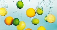 Lemons and limes splashing in water