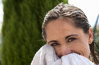 A Woman drying her face with a towel