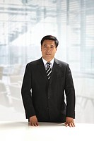 Businessman standing by table,looking