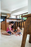 Mother playing with son on floor in kitchen