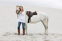 White horse, blond woman, beach, sand
