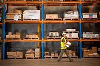 Warehouse Worker Walking Past Shelves