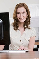Germany, Munich, young woman working in office, smiling, portrait