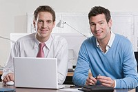Germany, Munich, two businessmen in office using laptop, smiling, portrait