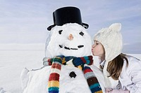 Germany, Bavaria, Munich, Girl 8_9 kissing snowman, side view, eyes closed, portrait